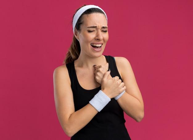 Schmerzende junge hübsche sportliche frau mit stirnband und armbändern, die das handgelenk mit geschlossenen augen hält