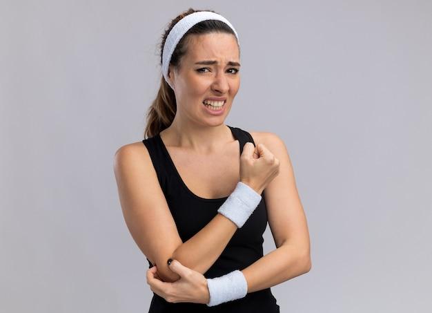 Schmerzende junge hübsche sportliche frau mit stirnband und armbändern, die den ellbogen berühren