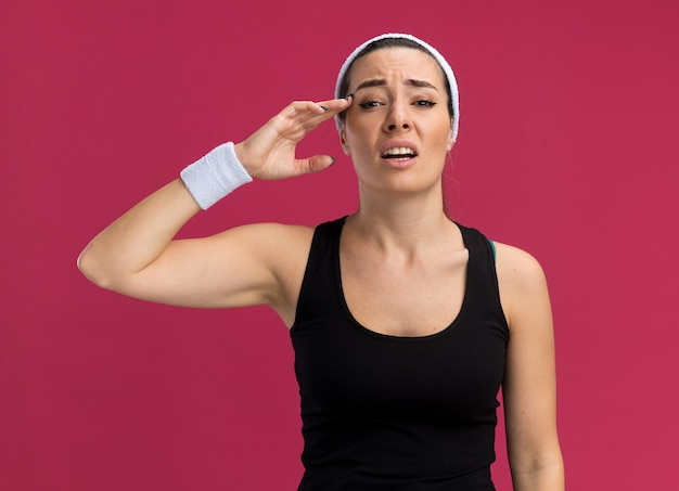 Schmerzende junge hübsche sportliche frau mit stirnband und armbändern, die den kopf berühren