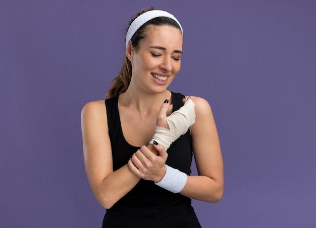 Schmerzende junge hübsche sportliche frau mit stirnband und armbändern, die ein verletztes handgelenk halten, das mit einem verband mit geschlossenen augen umwickelt ist