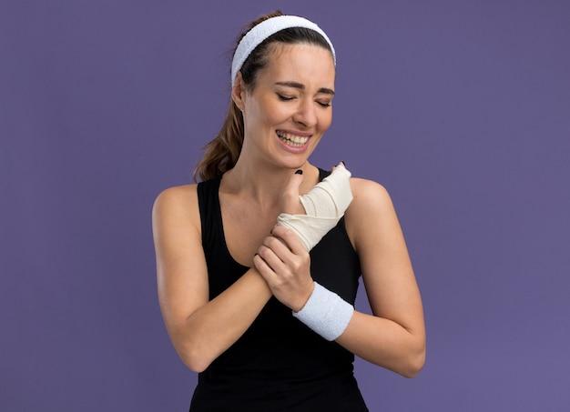 Schmerzende junge hübsche sportliche frau mit stirnband und armbändern, die ein verletztes handgelenk mit einem verband mit geschlossenen augen hält