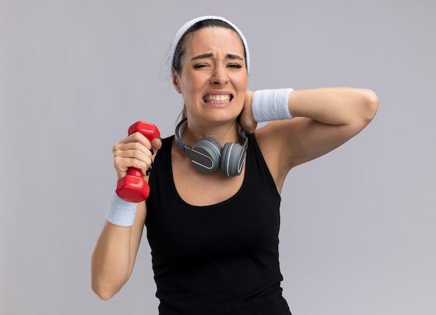 Schmerzende junge hübsche sportliche frau mit stirnband und armbändern, die hantel mit kopfhörern um den hals hält und die hand am hals hält