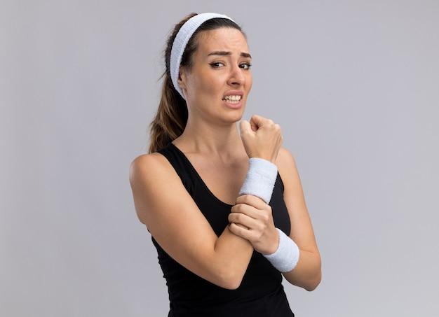 Schmerzende junge hübsche sportliche frau mit stirnband und armbändern mit handgelenk