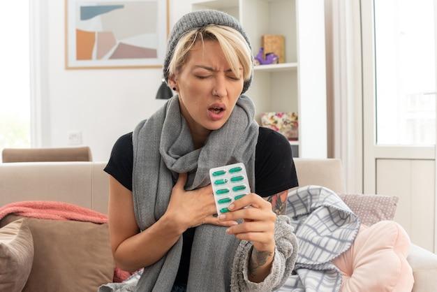 Schmerzende junge kranke slawische frau mit schal um den hals mit wintermütze, die hand auf die brust legt und medizinblisterpackung auf der couch im wohnzimmer hält