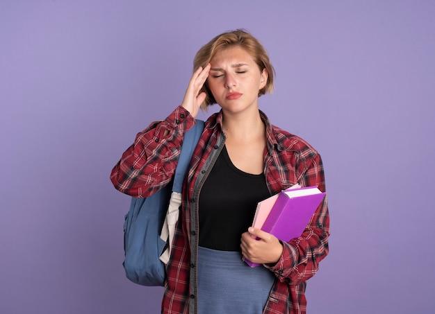 Schmerzende junge slawische studentin mit rucksack, die hand auf die stirn legt und buch und notizbuch hält