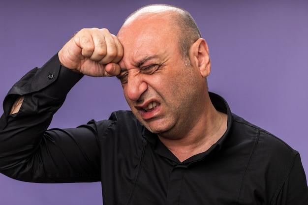 Schmerzender erwachsener kranker kaukasischer mann legt faust auf stirn isoliert auf lila wand mit kopienraum