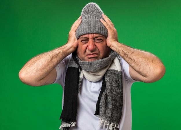 Schmerzender erwachsener kranker kaukasischer mann mit schal um den hals mit wintermütze, der den kopf isoliert auf grüner wand mit kopienraum hält