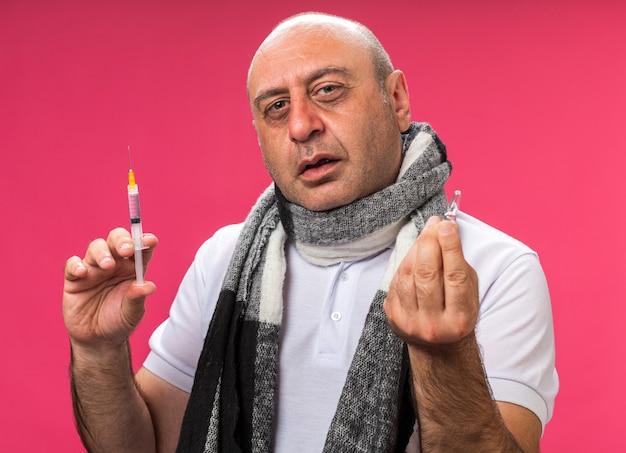 Schmerzender erwachsener kranker kaukasischer mann mit schal um hals hält spritze und ampulle lokalisiert auf rosa wand mit kopienraum