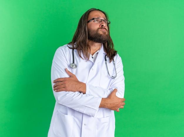 Schmerzender erwachsener männlicher arzt, der ein medizinisches gewand und ein stethoskop mit brille trägt und die hände am arm und am ellbogen nach oben gekreuzt hält