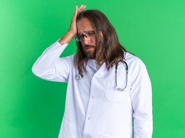 Schmerzender erwachsener männlicher arzt mit medizinischem gewand und stethoskop mit brille, der die hand auf dem kopf hält und isoliert auf die grüne wand schaut