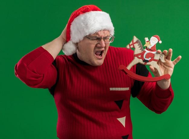 Schmerzender erwachsener mann, der brille und weihnachtsmannhut hält, der weihnachtsmann auf schaukelpferdfigur hält, die es betrachtet, die hand hinter dem kopf hält, der kopfschmerz lokalisiert auf grünem hintergrund hat