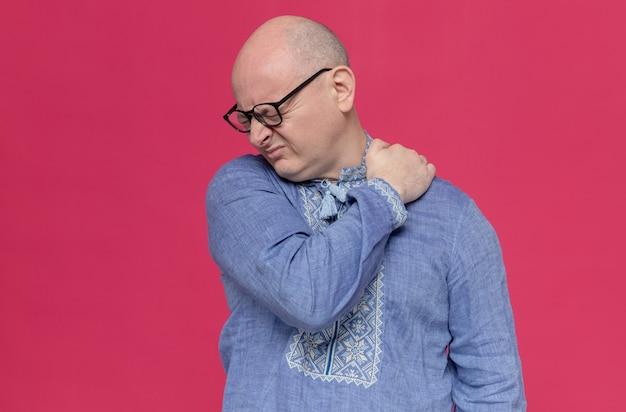 Schmerzender erwachsener slawischer mann im blauen hemd mit brille, der hand auf seine schulter legt