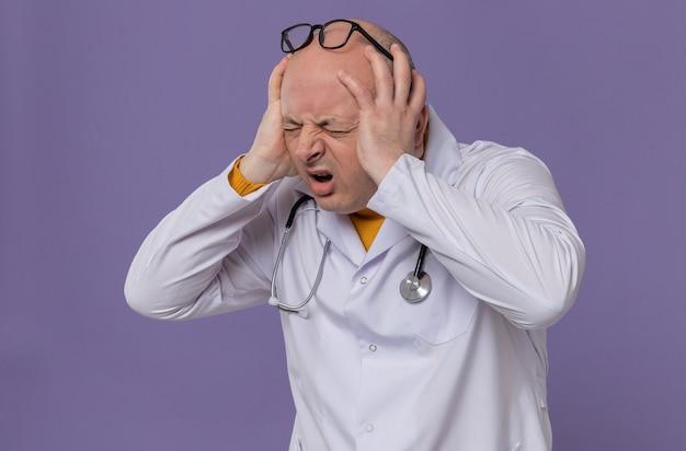Schmerzender erwachsener slawischer mann mit brille in arztuniform mit stethoskop, der die hände auf den kopf legt
