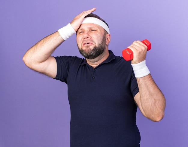 Schmerzender erwachsener slawischer sportlicher mann, der stirnband und armbänder trägt, die hand auf die stirn setzen und hantel lokalisiert auf lila wand mit kopienraum halten