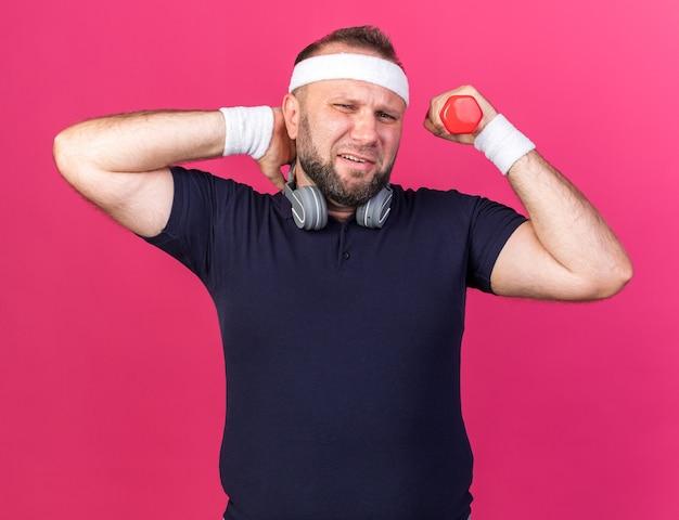 Schmerzender erwachsener slawischer sportlicher mann mit kopfhörern, die stirnband und armbänder tragen, die hantel halten und hand auf seinen hals legen, der auf rosa wand mit kopienraum isoliert ist