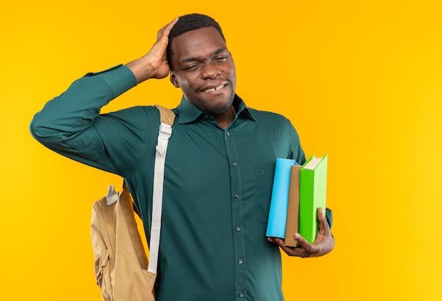 Schmerzender junger afroamerikanischer student mit rucksack, der bücher hält und die hand auf den kopf legt, isoliert auf oranger wand mit kopierraum