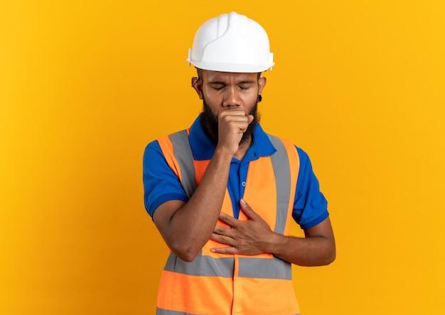 Schmerzender junger baumeister in uniform mit schutzhelm, der isoliert auf orangefarbener wand mit kopienraum hustet