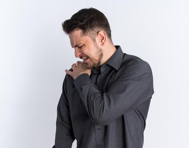 Schmerzender junger blonder gutaussehender mann, der die hand auf der schulter hält und den kopf zur seite dreht und nach unten schaut
