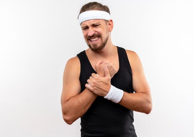 Schmerzender junger, gutaussehender, sportlicher mann mit stirnband und armbändern, der sein handgelenk hält, isoliert auf weiße wand mit kopierraum