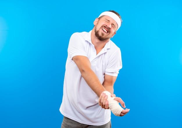 Schmerzender junger, gutaussehender, sportlicher mann mit stirnband und armbändern, der sein verletztes handgelenk mit verband umwickelt hält, mit geschlossenen augen isoliert auf blauer wand mit kopierraum