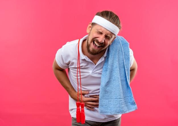 Schmerzender junger, gutaussehender, sportlicher mann mit stirnband und armbändern, der seinen bauch mit geschlossenen augen mit springseil und handtuch auf seinen schultern hält, isoliert auf rosafarbener wand mit kopierraum