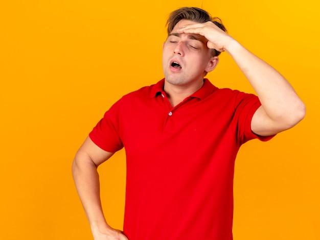 Schmerzender junger hübscher blonder kranker mann, der hand auf taille hält, die stirn berührt, die kopfschmerzen mit geschlossenen augen lokalisiert auf orange hintergrund mit kopienraum hat