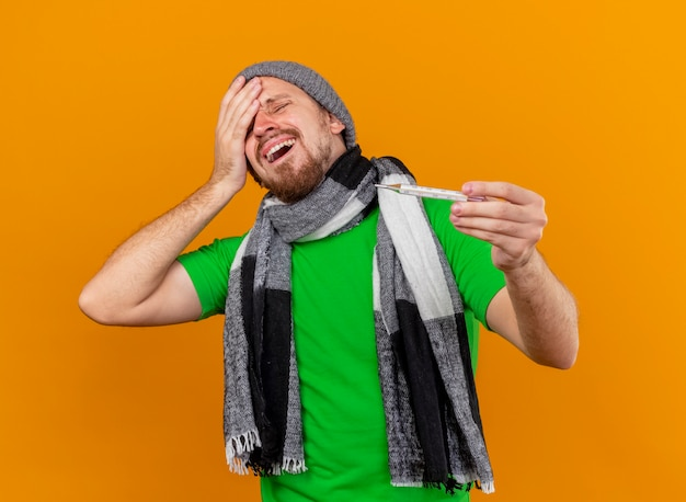 Schmerzender junger hübscher slawischer kranker mann, der wintermütze und schal hält, die thermometer-berührungskopf mit geschlossenen augen tragen, die auf orange wand lokalisiert sind