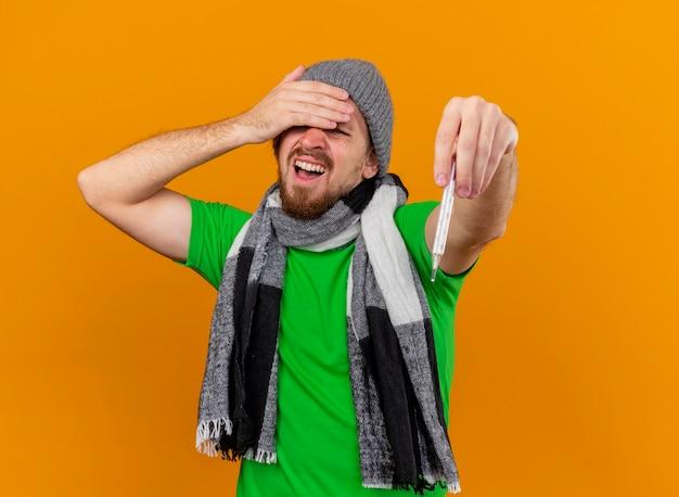 Schmerzender junger hübscher slawischer kranker mann, der wintermütze und schal trägt, die thermometer ausstrecken, das hand auf stirn lokalisiert auf orange wand mit kopienraum hält