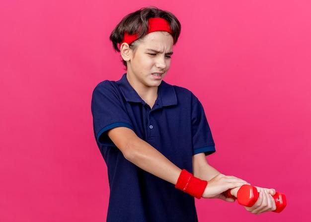 Schmerzender junger hübscher sportlicher junge, der stirnband und armbänder mit zahnspangen hält, die hantel betrachten und hand auf handgelenk lokalisiert auf purpurroter wand mit kopienraum setzen