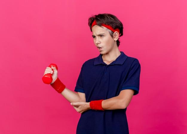 Schmerzender junger hübscher sportlicher junge, der stirnband und armbänder mit zahnspangen trägt, die gerade halten hantel, die hand auf ellbogen lokalisiert auf purpurrotem hintergrund mit kopienraum schaut
