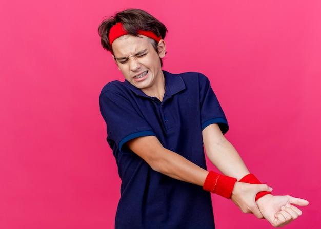 Schmerzender junger hübscher sportlicher junge, der stirnband und armbänder mit zahnspangen trägt, die handgelenk lokalisiert auf purpurroter wand mit kopienraum halten