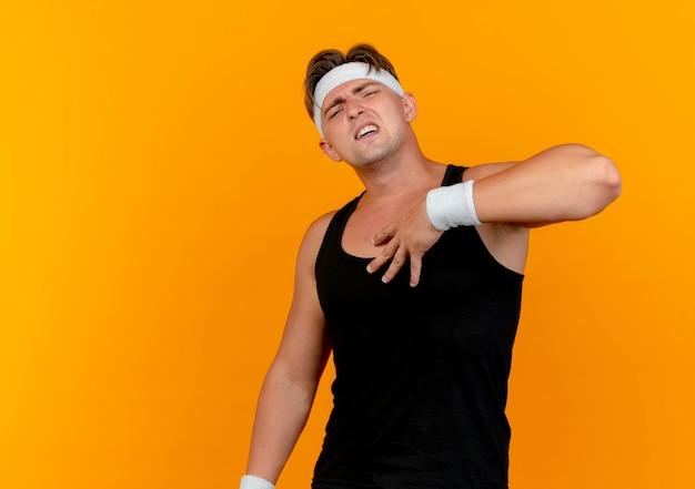 Schmerzender junger hübscher sportlicher mann, der stirnband und armbänder trägt, die hand auf brust lokalisiert auf orange mit kopienraum setzen
