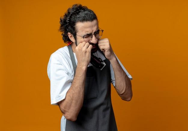 Schmerzender junger kaukasischer männlicher friseur, der uniform und brille trägt, die haarschneidemaschinen hält und die hände auf die wangen legt, die mit geschlossenen augen an zahnschmerzen leiden