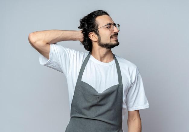 Schmerzender junger kaukasischer männlicher friseur mit brille und welligem haarband in uniform, der die hand mit geschlossenen augen hinter den kopf legt
