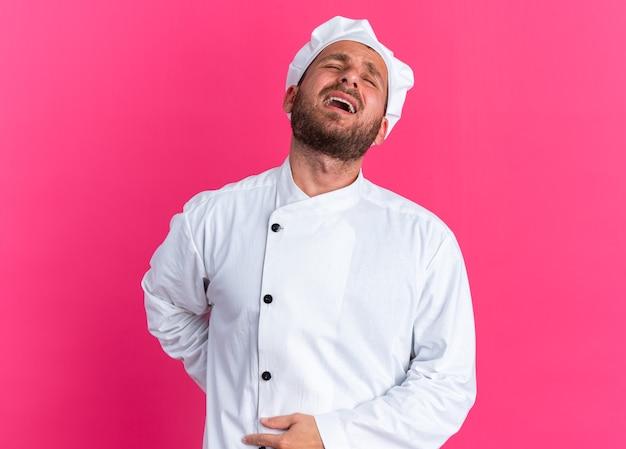 Schmerzender junger kaukasischer männlicher koch in kochuniform und mütze, der die hand mit geschlossenen augen auf rücken und bauch hält