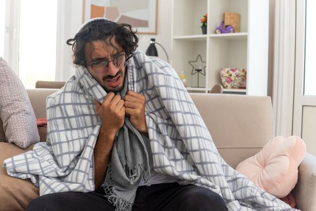 Schmerzender junger kranker kaukasischer mann in optischer brille, eingewickelt in plaid mit schal um den hals, der auf der couch im wohnzimmer sitzt