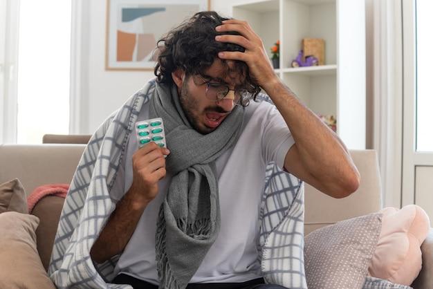 Schmerzender junger kranker kaukasischer mann in optischer brille, eingewickelt in plaid mit schal um den hals, der die hand auf den kopf legt und die blisterpackung hält, die auf der couch im wohnzimmer sitzt