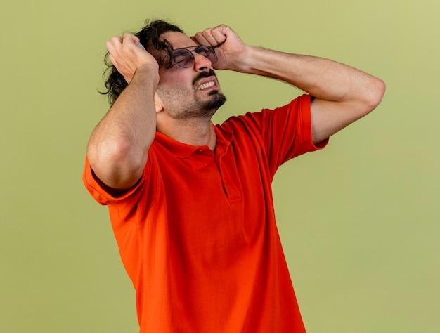 Schmerzender junger kranker mann, der eine brille hält, die kopf hält, der unter kopfschmerzen mit geschlossenen augen leidet, die auf olivgrüner wand lokalisiert werden