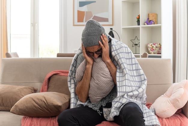 Schmerzender junger kranker mann in optischer brille, eingewickelt in plaid mit schal um den hals, der eine wintermütze trägt und die hände auf den kopf legt und das kissen auf der couch im wohnzimmer hält