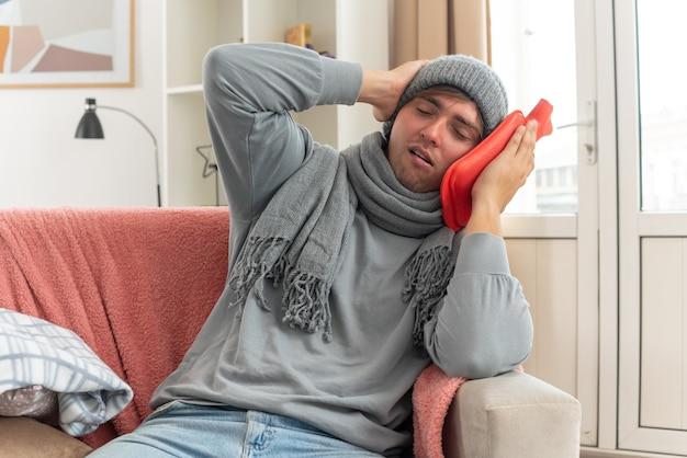 Schmerzender junger kranker mann mit schal um den hals, der eine wintermütze trägt, die hand auf den kopf legt und eine wärmflasche auf der couch im wohnzimmer hält