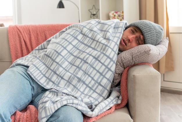 Schmerzender junger kranker mann mit schal um den hals, der eine wintermütze trägt, die in plaid gehüllt auf der couch im wohnzimmer liegt?