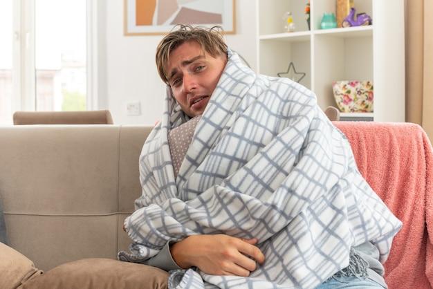 Schmerzender junger kranker mann mit schal um den hals, der in kariertes kissen gewickelt ist, das auf der couch im wohnzimmer sitzt