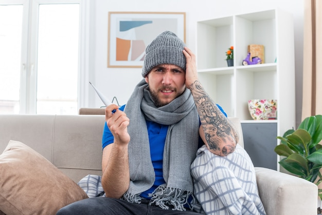 Schmerzender junger kranker mann mit schal und wintermütze, der auf dem sofa im wohnzimmer sitzt und ein thermometer hält, das die hand auf dem kopf hält
