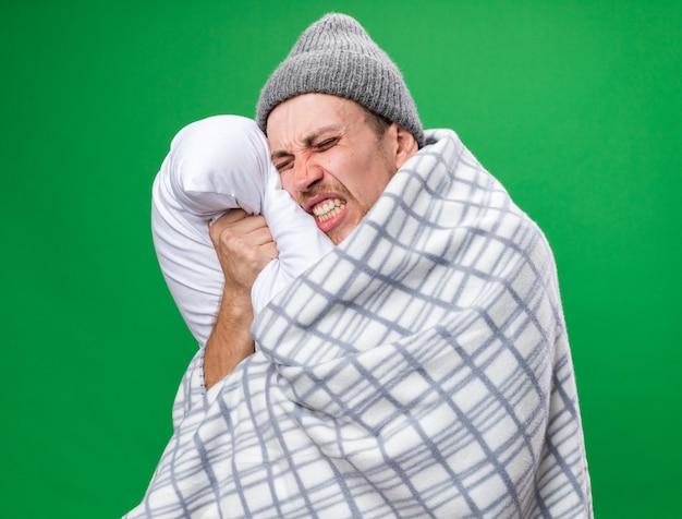 Schmerzender junger kranker slawischer mann mit schal um den hals, der in plaid gehüllt ist und wintermütze trägt, steht mit geschlossenen augen, die kissen halten