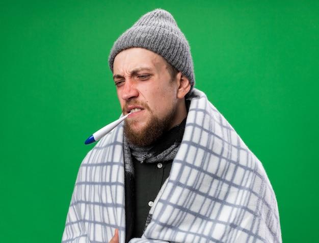 Schmerzender junger kranker slawischer mann mit schal um den hals, eingewickelt in karierte wintermütze mit thermometer im mund