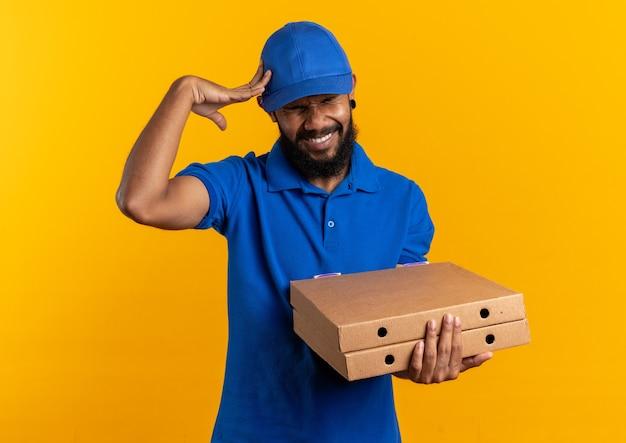 Schmerzender junger lieferer, der pizzakartons hält und die hand auf den kopf legt, isoliert auf oranger wand mit kopierraum
