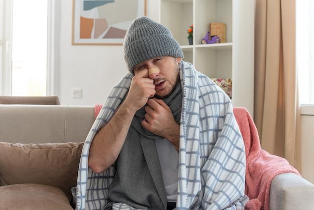 Schmerzender kranker mann mit nasenstreifen und mit schal um den hals, der eine wintermütze trägt, die in plaid gehüllt ist und den finger auf die nase legt, die auf der couch im wohnzimmer sitzt