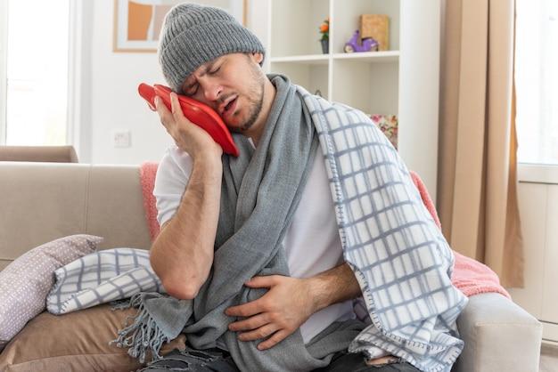 Schmerzender kranker mann mit schal um den hals, der eine wintermütze trägt, die in kariertes halten gewickelt ist und den kopf auf die wärmflasche setzt, die auf der couch im wohnzimmer sitzt