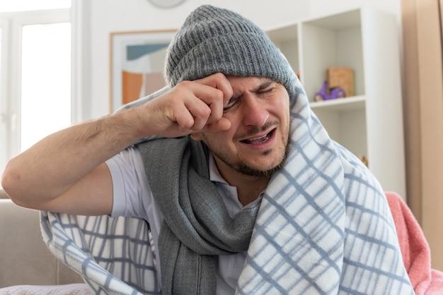 Schmerzender kranker mann mit schal um den hals, der wintermütze in plaid gewickelt trägt und seine hand auf den kopf legt, mit geschlossenen augen auf der couch im wohnzimmer sitzend