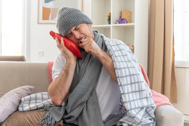 Schmerzender kranker slawischer mann mit schal um den hals, der eine in plaid gewickelte wintermütze trägt, die seine hand nah am mund hält und eine wärmflasche auf der couch im wohnzimmer hält